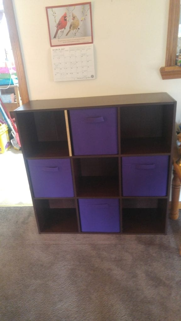 Photo: square 9x9 book case with four purple canvas boxes in alternating spots; one shelf with the rough spot showing