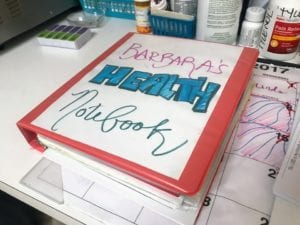 Photo: Coral red binder with a white piece of paper on the front that reads Barbara
