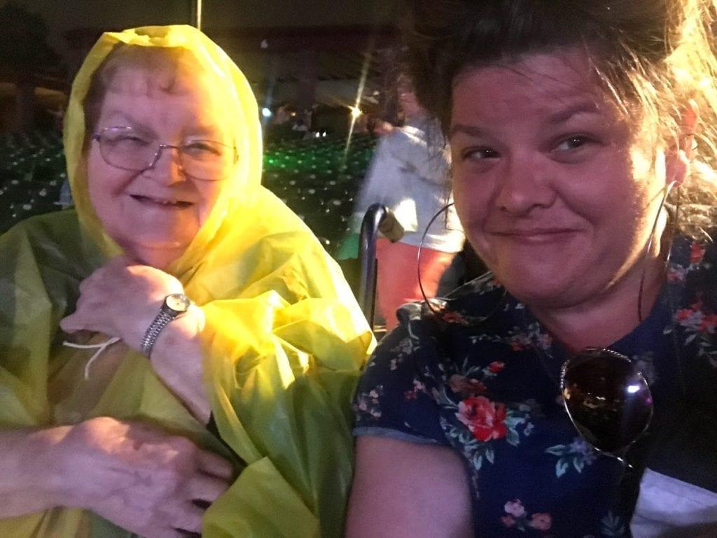 Photo: Barbara and Rachel in the rain, smiling, Barbara wearing a bright yellow poncho